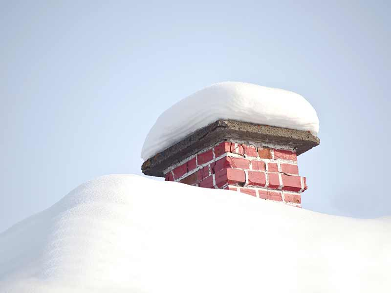 Snow sitting on top of chimney that requires removal in Ottawa