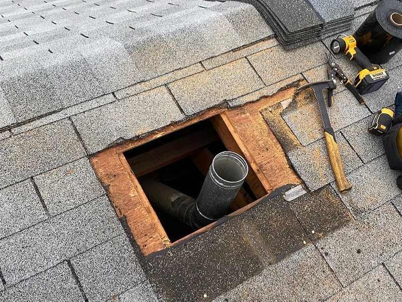 Hole opened in roof during chimney removal requiring shingle and flashing repair